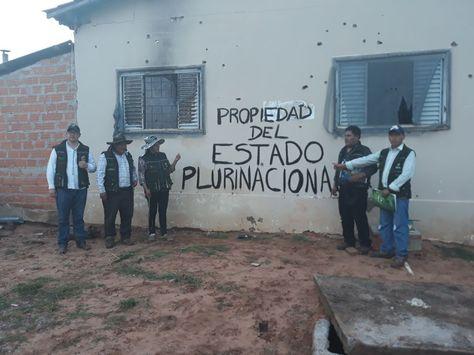 Funcionarios del INRA posan frente a una pared que aún tiene las huellas del impacto de los proyectiles.