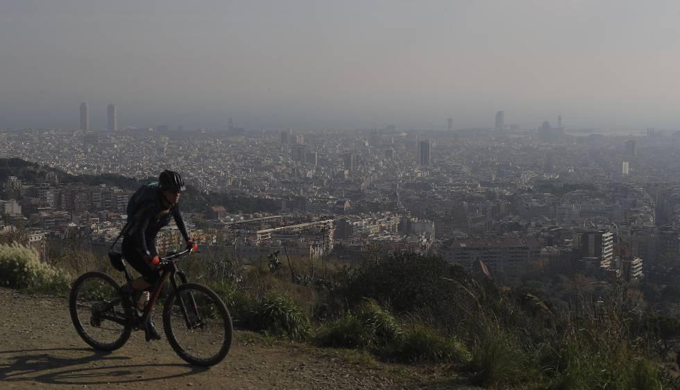 Una ciclista por la carretera de les Aigües (Barcelona) durante un episodio de contaminación