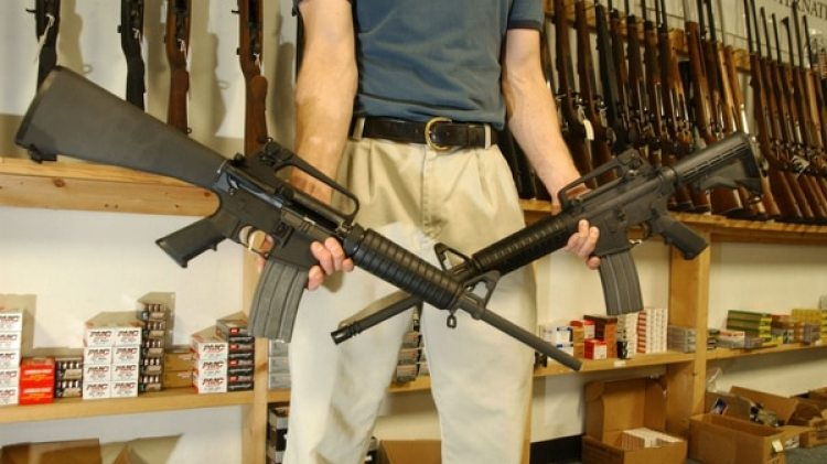 El empleado de una tienda de armas muestra dos rifles automáticos (Getty Images)