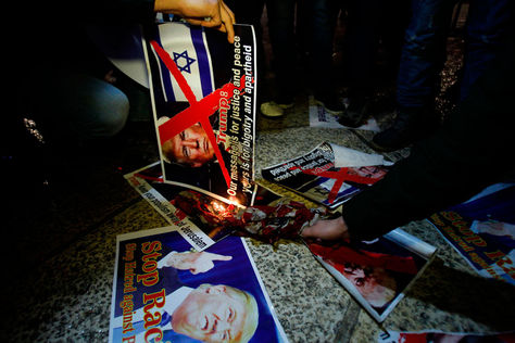 Manifestantes palestinos queman carteles del presidente de EEUU en la Plaza del Pesebre de Belén.