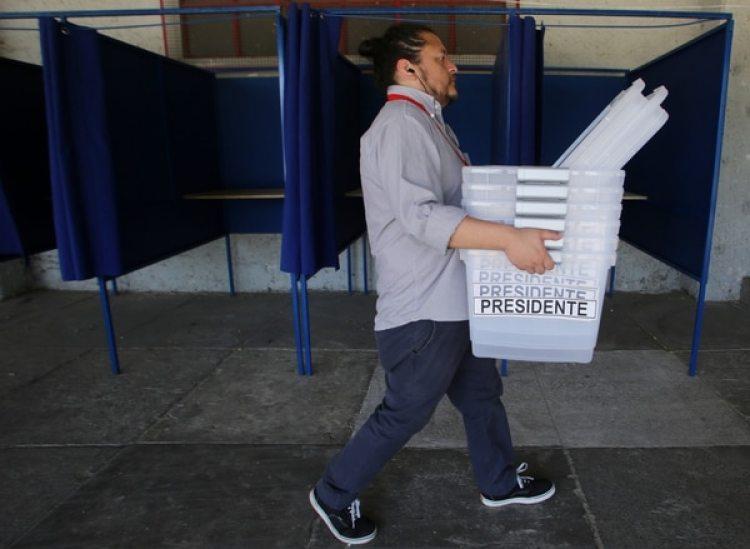 Un empleado carga urnas en el Estadio Nacional (AFP)