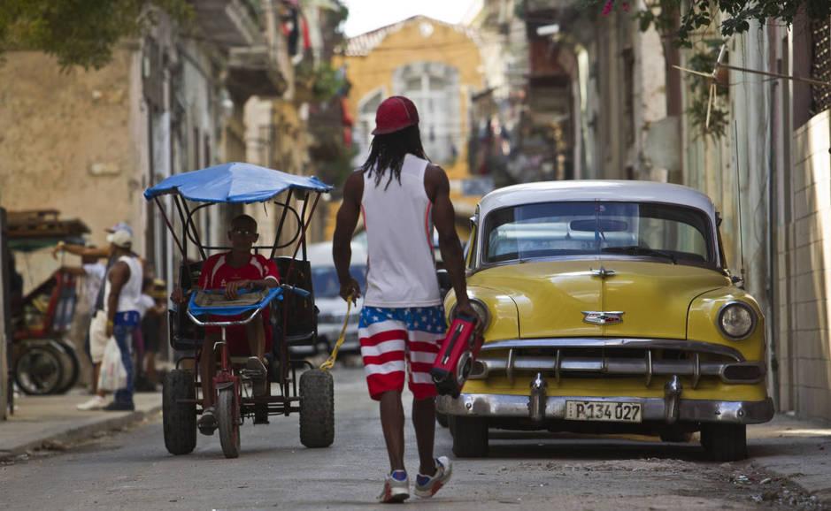 Un hombre camina cerca a una vehículo clásico y un bicitaxi en La Habana, el 26 de diciembre de 2017. (Reuters)