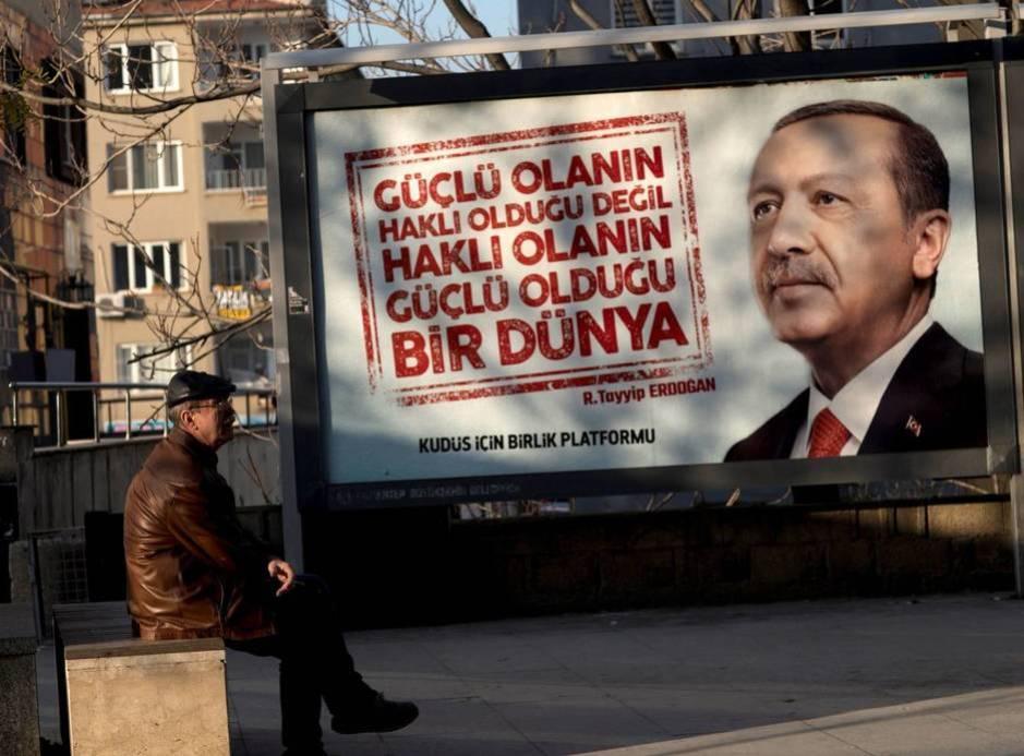Un hombre se sienta frente a un cartel con la imagen del presidente turco, Recep Tayyip Erdogan, en Gaziantep (Turquía), en diciembre de 2017. (EFE)