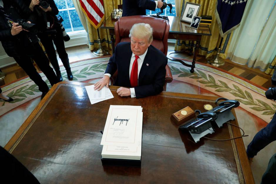 El presidente estadounidense Donald firma una ley ante la prensa en el Despacho Oval, el 22 de diciembre de 2017. (Reuters)