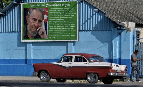 Un viejo automóvil junto a un cartel del difunto líder cubano Fidel Castro en La Habana. Foto: AFP