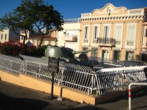 For some reason, a small tank has been trapped in this white picket fence.