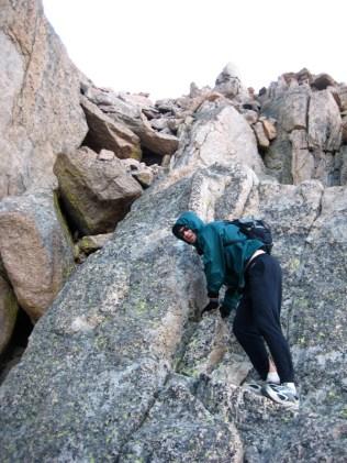 Mike downclimbing some very tricky ground near Clark's Arrow.