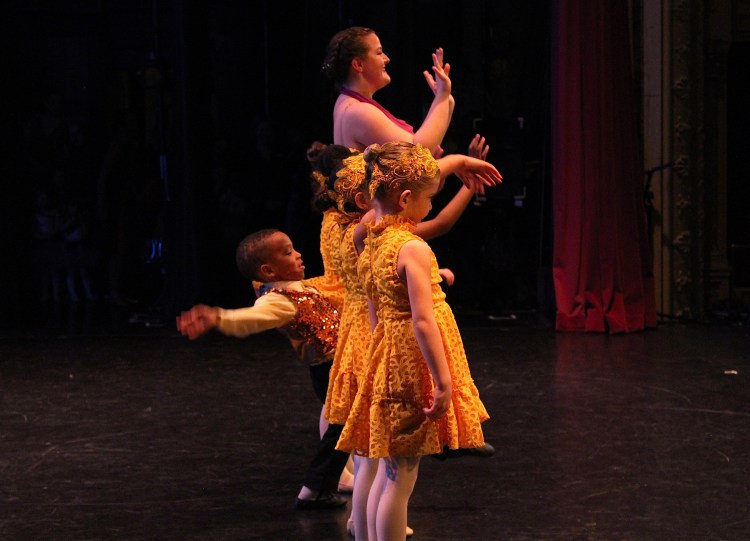 Young dancers on stage and a little boy doing his own thing