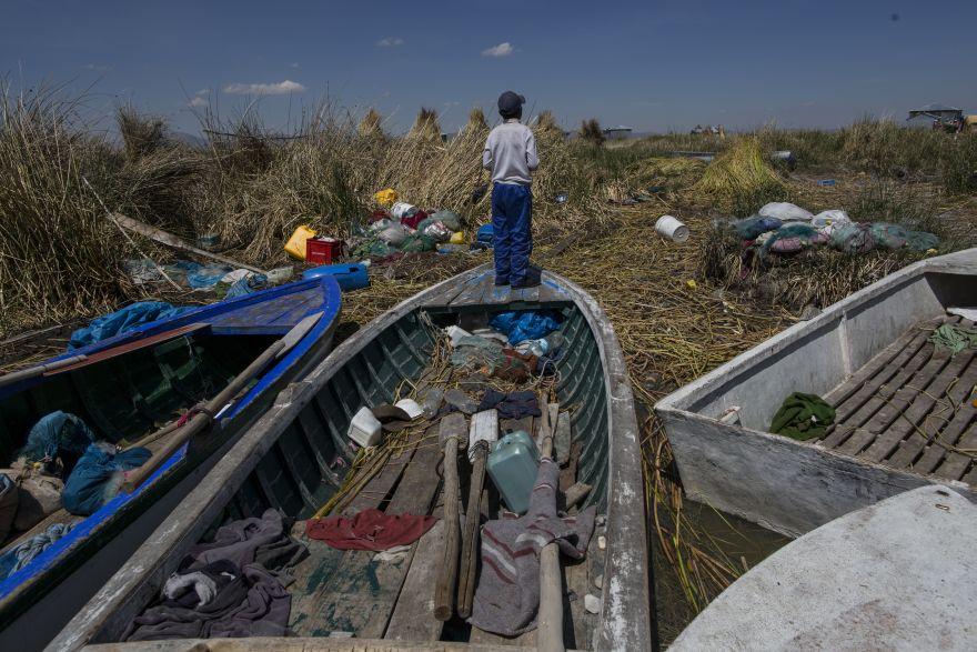 Un niño se encuentra en un barco pesquero en la costa llena de basura del lago Titicaca en Kapi Cruz Grande, en la región de Puno, Perú. Las ranas de agua Titicaca de color de camuflaje que solían estar en abundancia, han disminuido en cantidad y han sido colocadas en una lista de animales en peligro crítico, elaborada por la Unión Internacional para la Conservación de la Naturaleza. Sólo quedan 10.000 ejemplares de dicho animal. (Foto: AP/Rodrigo Abd)