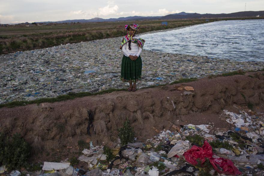 La activista ambientalista Maruja Inquilla posa para una foto junto a una planta municipal de tratamiento de residuos con agua que desemboca en el lago Titicaca.