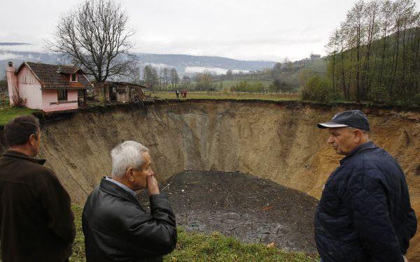 Pobladores de de Sanica, en Bosnia, visitan lo que antes era un lago, y ahora es un enorme agujero. La laguna estaba llena de peces y algas. (Foto: AP)