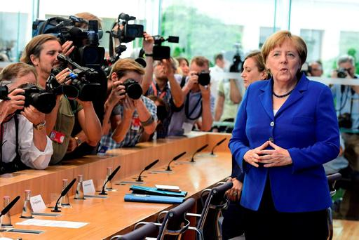 Chancellor Angela Merkel passes photographers as she arrives for a press conference in Berlin. Photo: Getty