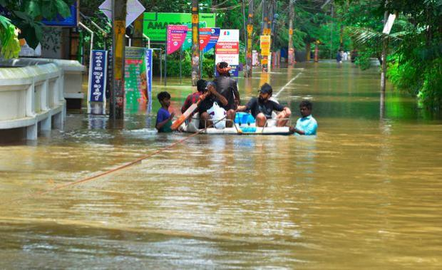 People move past a flooded area in Thrissur, in the southern Indian state of Kerala (AP Photo)