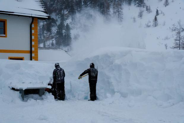 Two workers remove snow after a blizzard in the Austrian Alpine ski resort of Obertauern