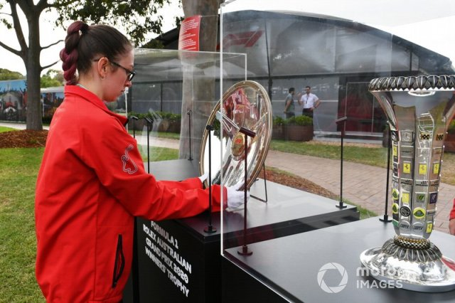 Paddock staff make preparations with the race trophy