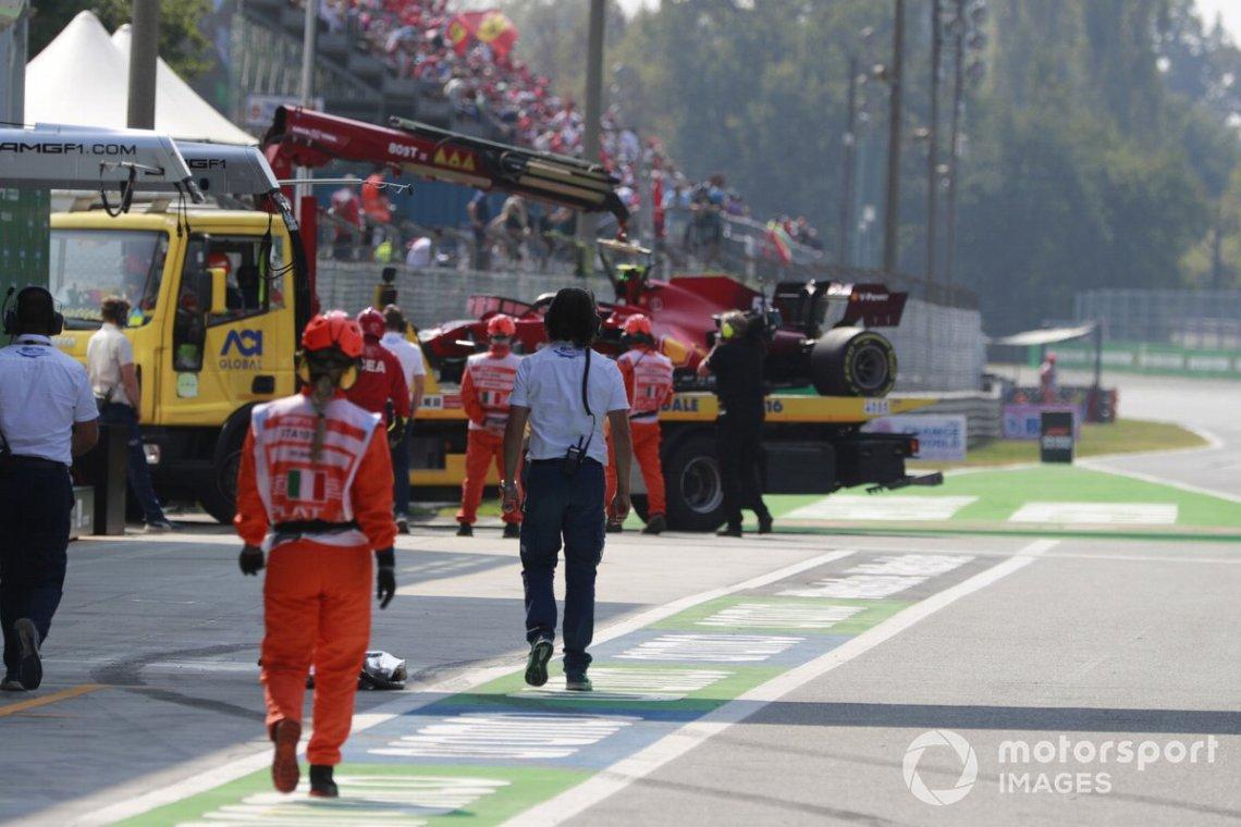 Marshals return the car of Carlos Sainz Jr., Ferrari SF21, to the pits