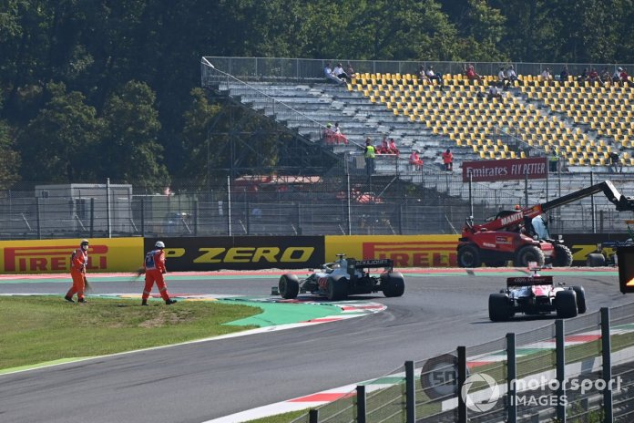 Los oficiales limpian la pista del monoplaza de Romain Grosjean, Haas VF-20, mientras pasa Kimi Raikkonen, Alfa Romeo Racing C39