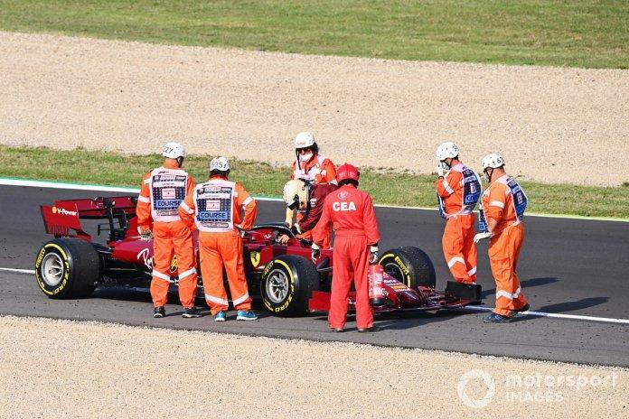 Los oficiales se reúnen alrededor del monoplaza parado de Sebastian Vettel, el Ferrari SF1000