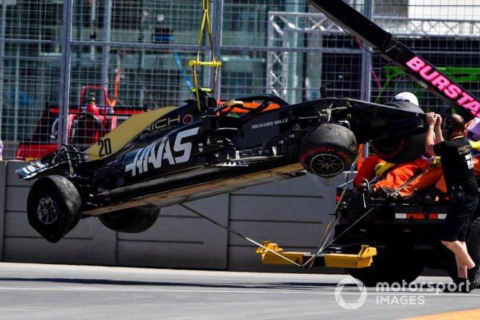 Oficiales retiran el coche dañado de Kevin Magnussen, Haas F1 Team VF-19, del circuito