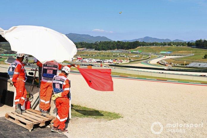 Los oficiales de pista agitan la bandera roja durante la FP2