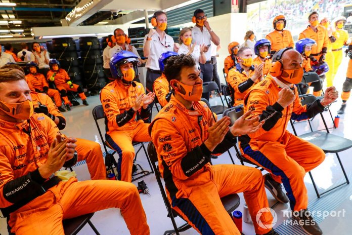 The McLaren pit crew cheer the efforts of their drivers at the start