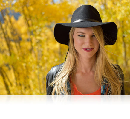 D5500 photo of a blonde woman in a black cowboy hat with trees in the background