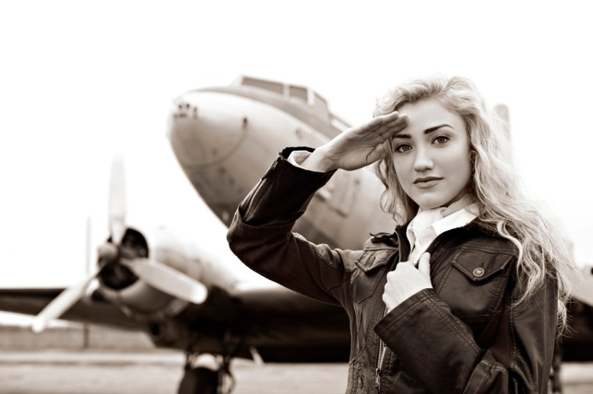 Photo of a model dressed as a pilot in front of an old plane in sepia tone, shot using the AF-S NIKKOR 50mm f/1.4G lens