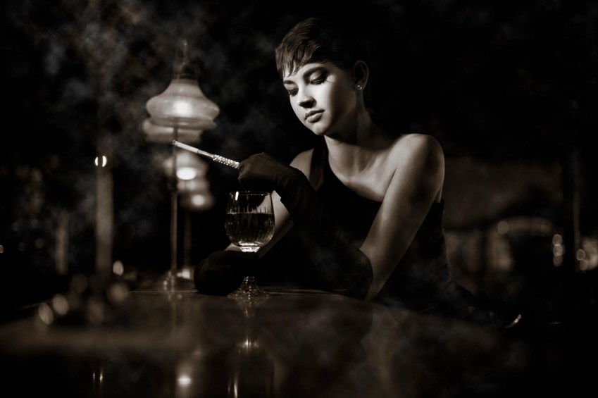 Photo of a woman sitting at a bar, low key, sepia tone, shot with the AF-S NIKKOR 50mm f/1.4G lens