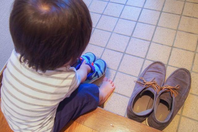 小さな子供が自分で靴を履いてお出かけする