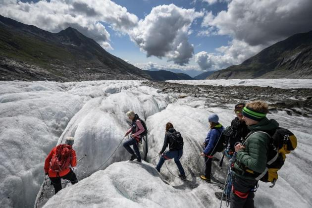 Teenagers walk on the Aletsch Glacier during a visit with Swiss glaciologist Matthias Huss (not pictured) on August 25, 2021. Photo: Fabrice Coffrini / AFP