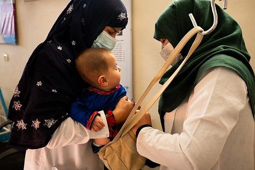 a midwife (left) and a nutrition counsellor weighing a baby at the Tangi Saidan clinic run by the Swedish Committee for Afghanistan, in Daymirdad district of Wardak province.