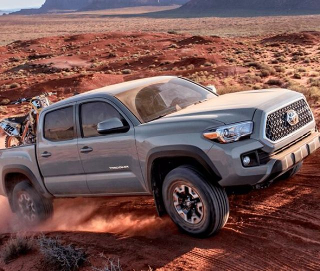 Front And Side View Of Gray  Toyota Tacoma Hauling Dirtbikes In Desert