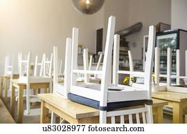 chair upside down on wall kitchen chairs rollers stock photograph of tables and clock table in cafe
