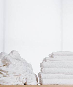 Stacks of unfolded and folded white laundry