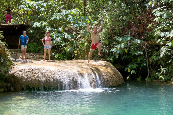 Swimming Holes Image: A group of travellers stands at a swimming hole; one is poised to jump in.