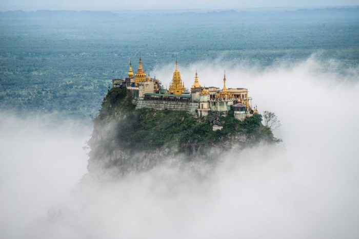 Destinations Worth Dreaming Image: A beautiful structure sits atop a mountain shrouded in mist.