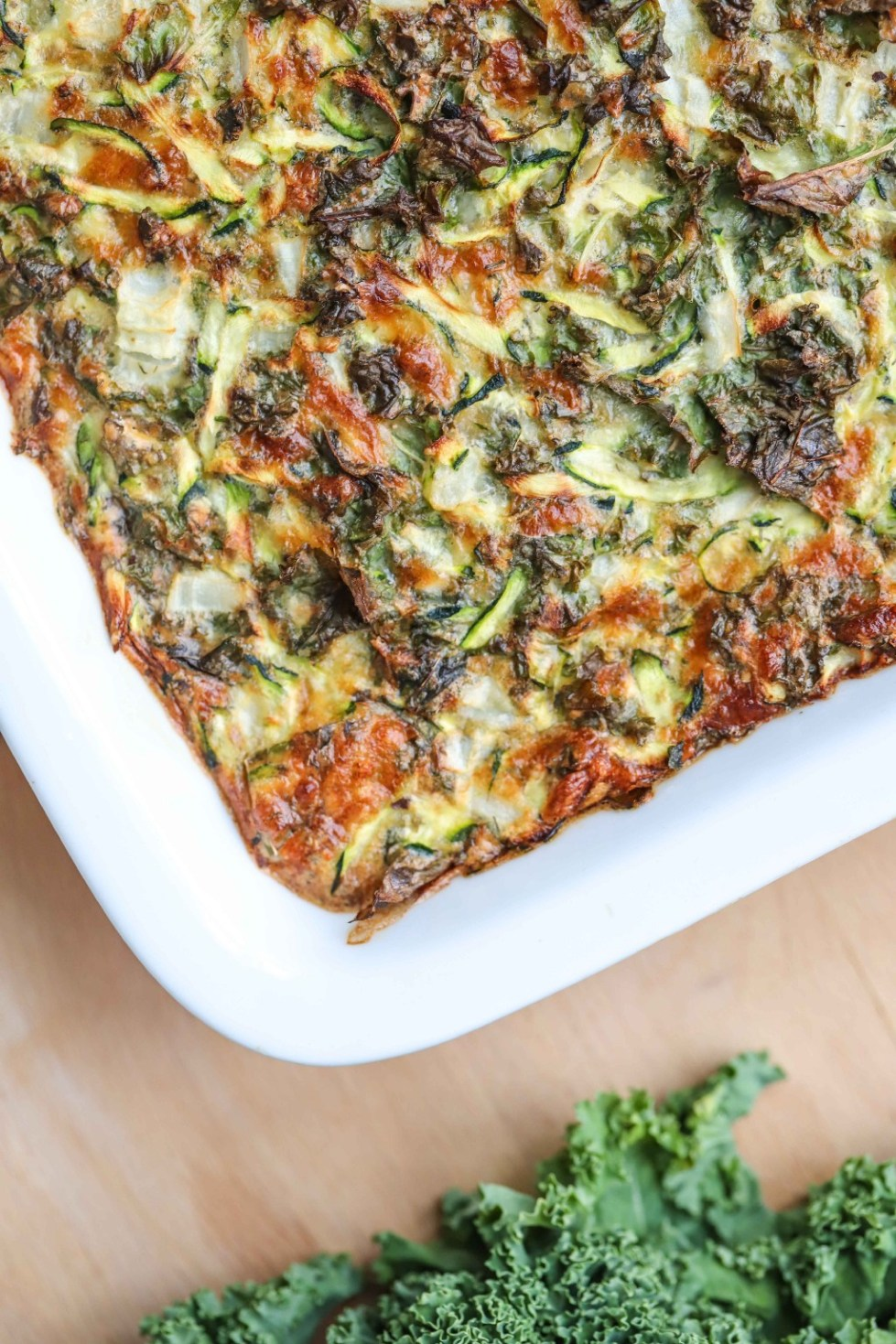 Zucchini and kale breakfast bake in a white baking dish on top of a wooden cutting board