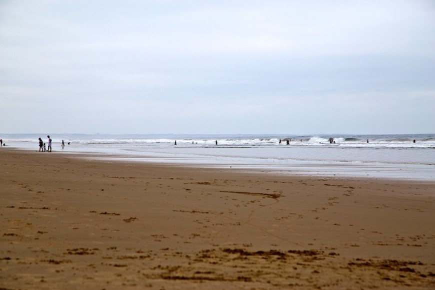 Best Surfing Beaches: People are enjoying the sand and surf of a long and wide stretch of beach.