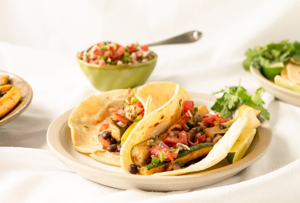 A white plate with two roasted vegetable tacos, garnished with cilantro.