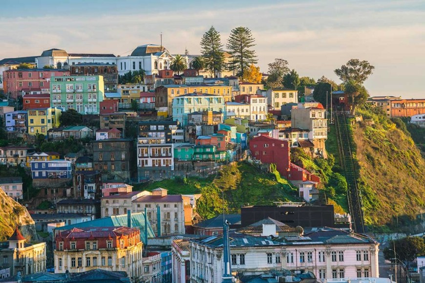 Destinations Worth Dreaming Image: Cubes of colourful buildings are present on a city hillside—the occasional green space or tree is present.