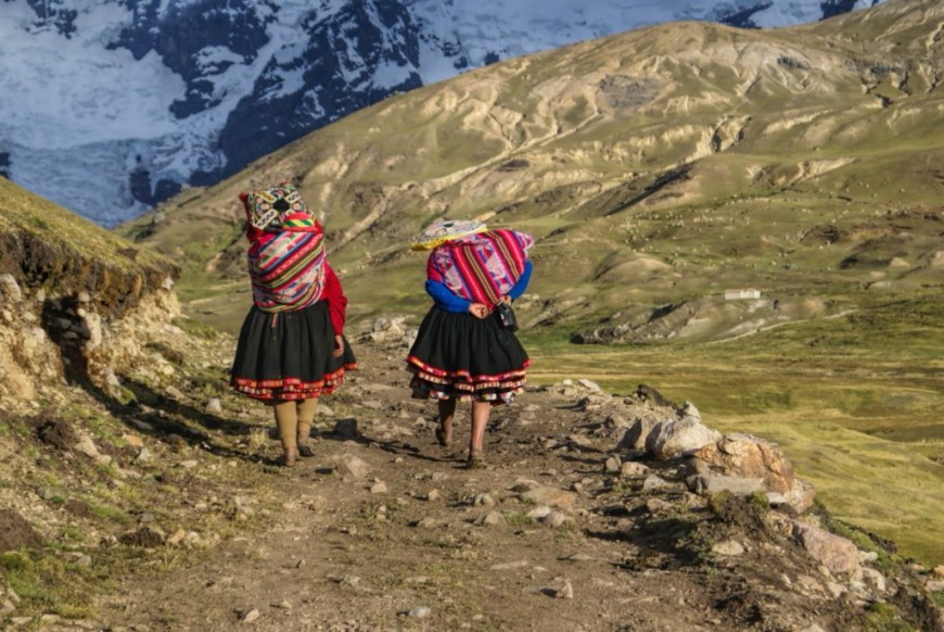 Central and South American Ruins Image: Two women have their backs to us. They are wearing colourful skirts, and are carrying equally colourful bundles on their backs as they walk down an incline in the Andes.