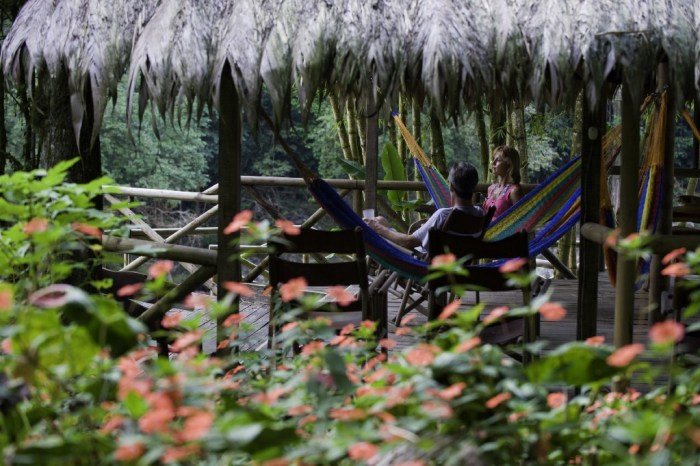 Eco-Friendly Costa Rica Image: A couple sits in two hammocks in an open-air structure covered by a leafy roof. They are talking and enjoying the surrounding jungle scenery.