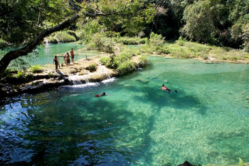 Swimming Holes Image: Several people are pictured taking in the view of the swimming holes, and enjoying a swim in their waters.