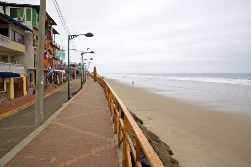 Best Surfing Beaches: Photograph of the city being divided from the nearby beach with a wooden railing and large stones.