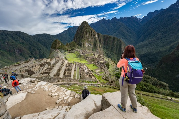 Central and South American Ruins Image: Travellers are staggered on different levels of a ruin at Machu Picchu. At the top most level, a woman wearing a backpack is poised to take a photograph.