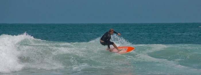Best Surfing Beaches: A surfer in a black two piece wetsuit rides a red surf board in the water.