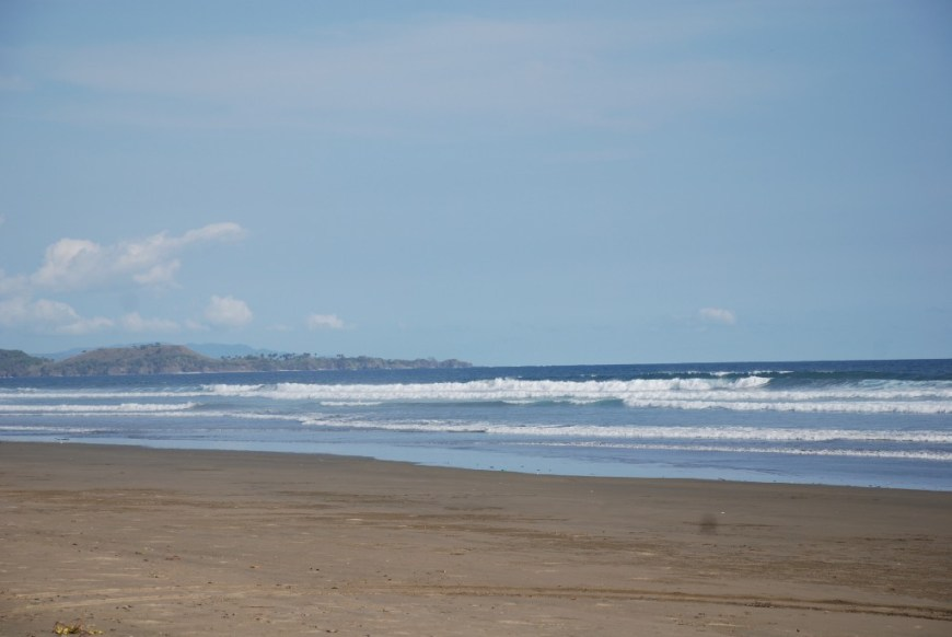 Best Surfing Beaches: The beach is empty, and waves are cresting highly as they roll in.
