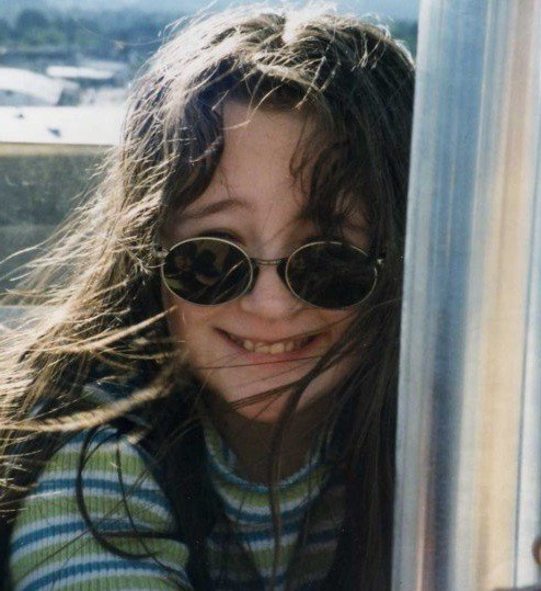[1998–2000ish: Kirsten on a Ferris Wheel during a sunny day, holding the pole in the middle; she has long hair blowing in her face, round John Lennon-eque glasses, a striped white/blue/green shirt, and she is smiling]