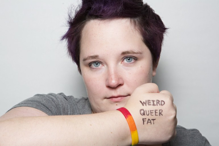 "[2016: a photo of Kirsten holding her right arm up in front of her mouth with her hand in a fist, back of the hand facing out with the words ""Weird Queer Fat"" written on it in black sharpie; a rainbow bracelet is on her wrist; she is making a neutral, though kind of sad, face with her blue eyes staring out piercingly; she has on a grey tee and has dark brownish purpleish hair spiked into a faux hawk]"
