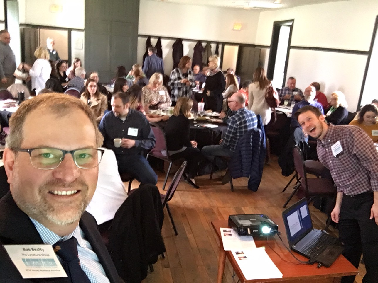 Bob Beatty takes a selfie image of the workshop room. He is in the bottom left corner of the frame wearing glasses with a large group of people seated around round tables behind him.